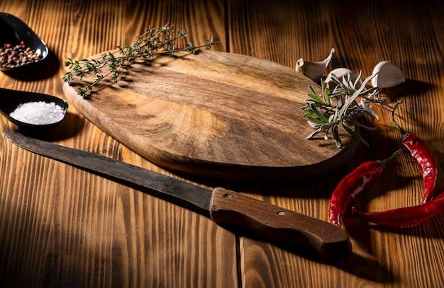 Экспозиция деревянного стола с ножом, перцем чили, чесноком и перцем на деревянный стол Premium Фотографии