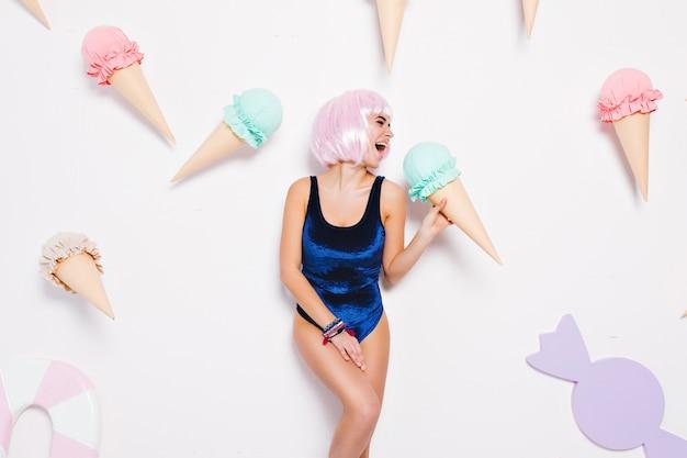 巨大なアイスクリームを楽しんでいる水着で、ピンクの髪型のカットでセクシーな若い女性の明るくポジティブな感情を表現します。お菓子、幸せ、遊び心のある魅力的なモデルです。 無料写真