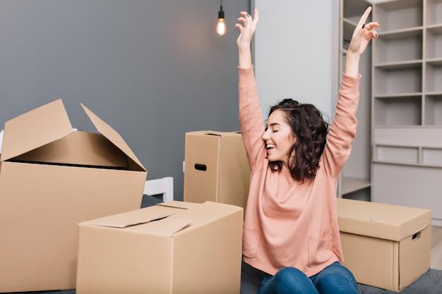 Выражая яркие истинные эмоции, позитив молодой красивой женщины с короткими брюнетными вьющимися волосами на кровати окружает картонные коробки в современной квартире. наслаждаюсь переездом, счастьем в новом доме Бесплатные Фотографии