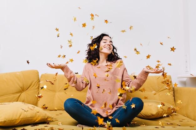 モダンなアパートのソファで落ちるティンセルを楽しんでいるカットの巻き毛の若いうれしそうな女性の真の肯定的な感情を表現します。ホームコサイン、喜び、笑顔 無料写真