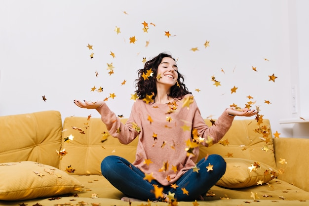 Expressing true positive emotions of young joyful woman with cut curly hair having fun in falling tinsels on couch in modern apartment. home cosines, joy, smiling Free Photo