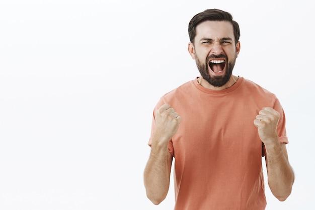 Expressive bearded man in orange tshirt Free Photo