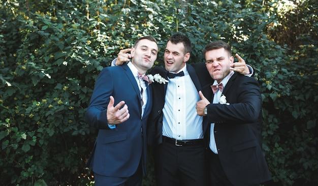 Expressive groomsmen posing in park Free Photo