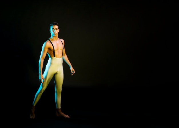 Expressive male ballet dancer performing in spotlight Free Photo