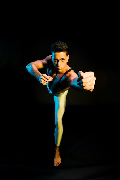 Expressive male ballet performer dancing in spotlight Free Photo