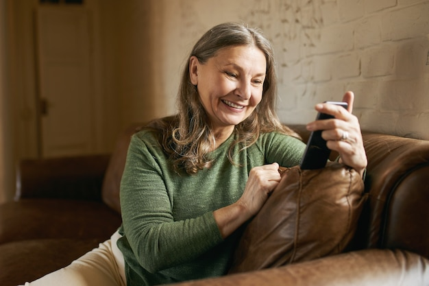 屋内でポーズをとる表情豊かな年配の女性 無料写真