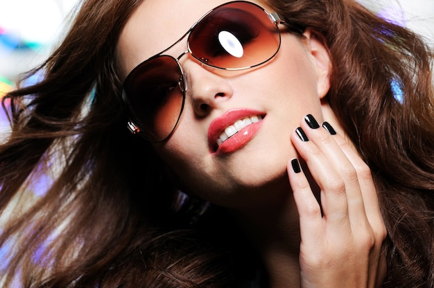 Expressive view of beautiful  brunette woman with modern brown fashion sunglasses Free Photo