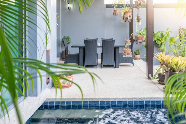 Exterior  and interior design showing tropical pool villa with green garden, with sun bed and blue sky Premium Photo