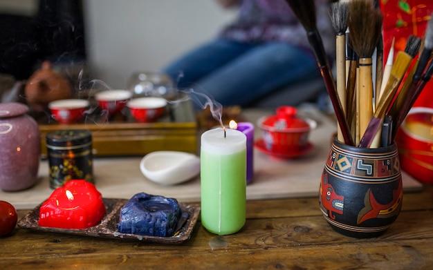 Потухшая свеча с дымом перед чайным сервизом на деревянном столе Бесплатные Фотографии