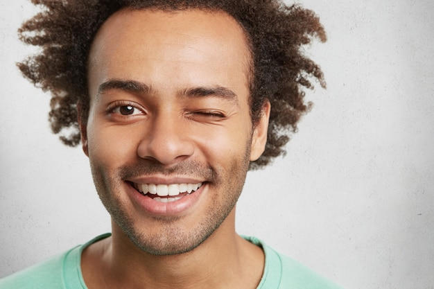 混合レースハンサムな男の極端なクローズアップはトレンディな髪型、心地よく笑顔、まばたき 無料写真