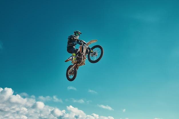 Экстремальная концепция, бросьте вызов самому себе. экстремальный прыжок на мотоцикле на фоне голубого неба с облаками. Premium Фотографии