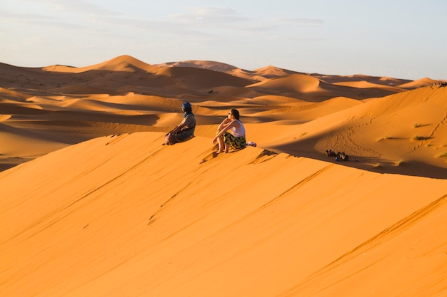 Extreme long shot of two people sitting on top of dune Free Photo