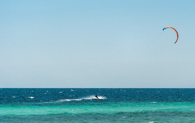 Extreme water sport - kitesurfing at sea on hot summer sunny day Premium Photo