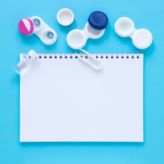 Eye care accessories on blue background with notebook mock-up Free Photo