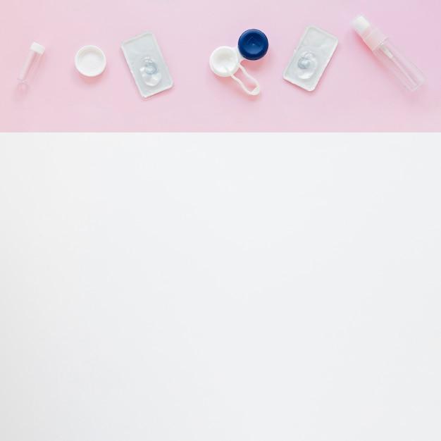 Аксессуары для ухода за глазами на розовом и белом фоне Бесплатные Фотографии