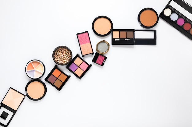 Eye shadows with facial powders on table Free Photo