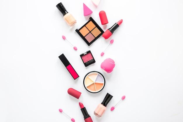 Eye shadows with lipsticks and nail polish on light table Free Photo
