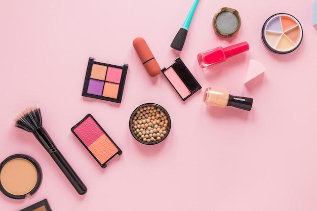 Eye shadows with nail polish on pink table Free Photo