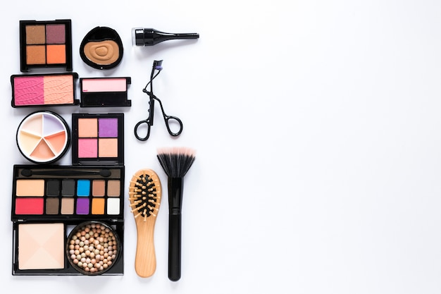 Eye shadows with powder brush and comb on table Free Photo