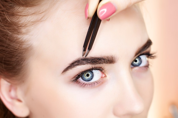Eyebrow plucking and painting in a beauty salon. Premium Photo