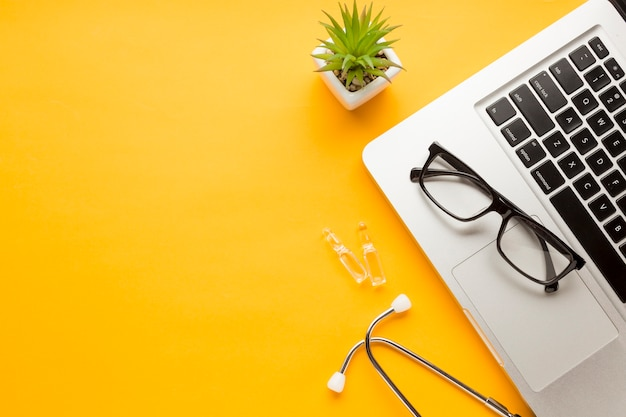 Eyeglass over laptop with ampoule; stethoscope with succulent plant against yellow backdrop Free Photo
