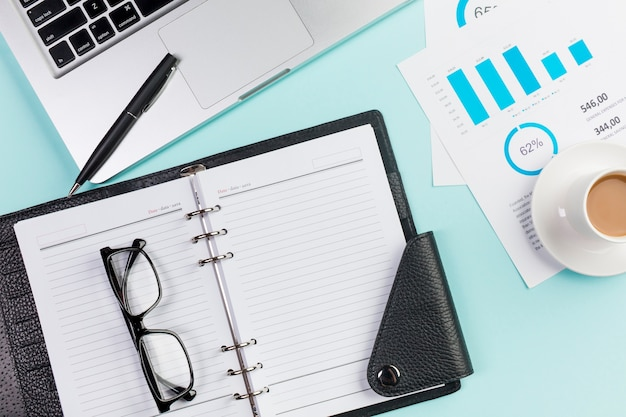 Eyeglasses on diary,laptop,pen,coffee cup and budget plan on office desk Free Photo