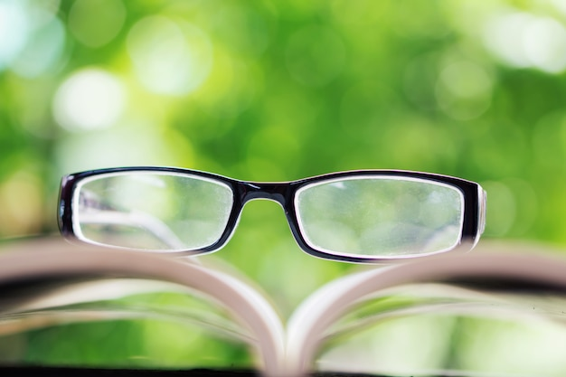 Eyeglasses on open book over nature Premium Photo