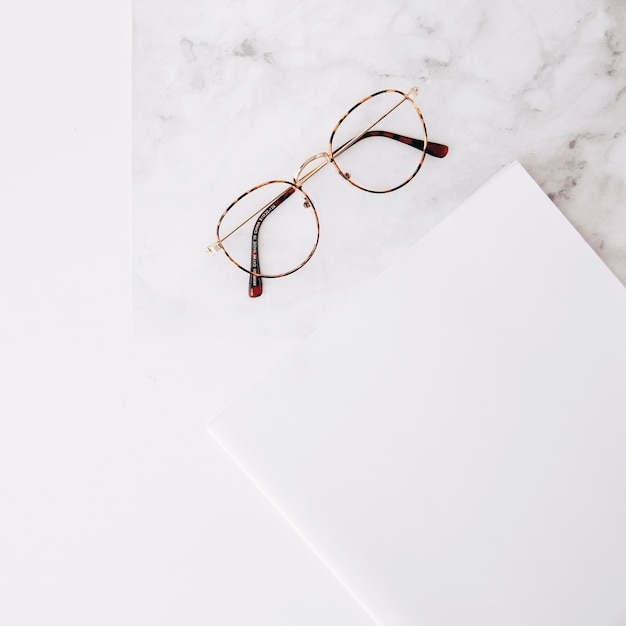 Eyeglasses and white paper on textured white backdrop Free Photo