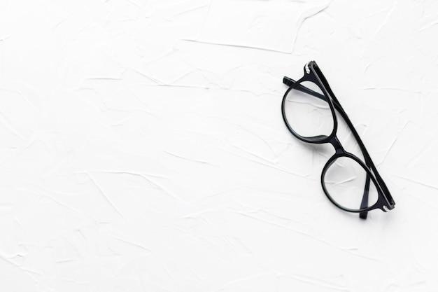 Очки с черной рамкой на белом фоне. очки для глаз. круглые очки с прозрачными линзами. закройте очки с размытой техникой. модный аксессуар. тема офтальмологии. плоская планировка. Premium Фотографии