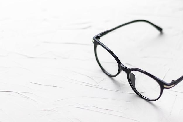 Очки с черной рамкой на белом фоне. очки для глаз. круглые очки с прозрачными линзами. закройте очки с размытой техникой. модный аксессуар. тема офтальмологии. Premium Фотографии