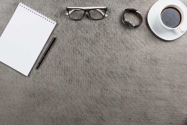 Eyeglasses; wrist watch; coffee cup and spiral notepad with pen on gray table top Free Photo