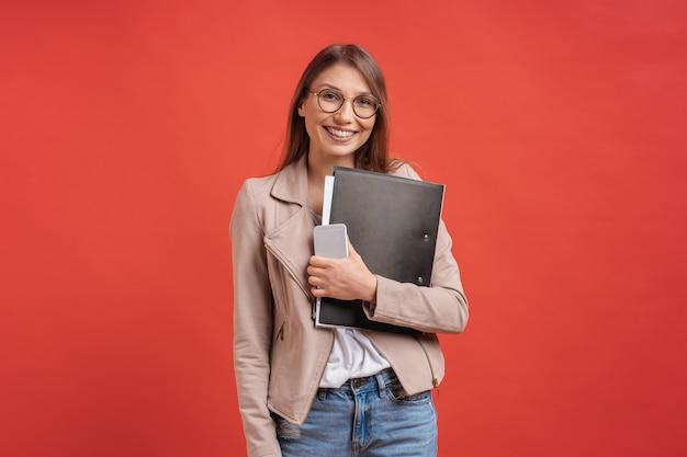 Молодой усмехаясь студент или интерн в eyeglasses стоя с папкой на красной стене. Бесплатные Фотографии