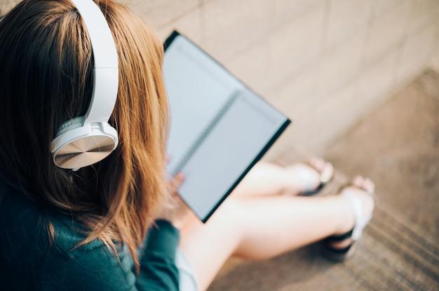 Усмехаясь женщина в книге чтения eyeglasses и слушать к музыке с наушниками в парке внешнем против солнечного света, концепции образа жизни города. Premium Фотографии