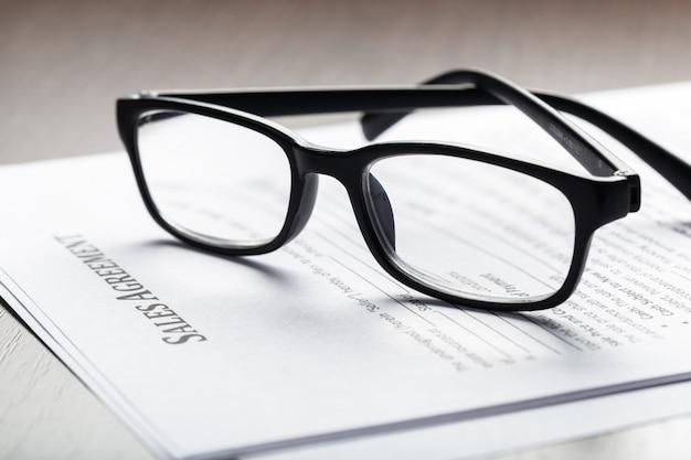 Закройте вверх по съемке eyeglasses на концепции дела документов документа контракта Premium Фотографии
