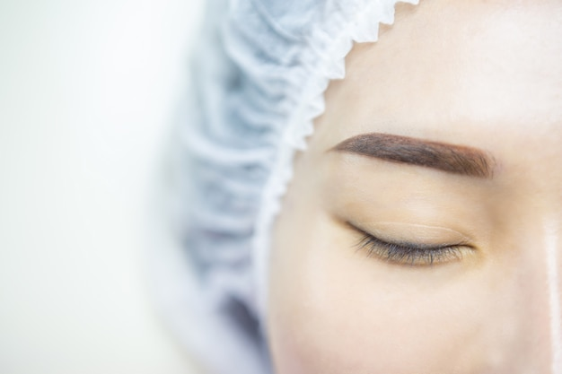 Eyelash extension. beautiful woman asia with long lashes in a beauty salon. Premium Photo