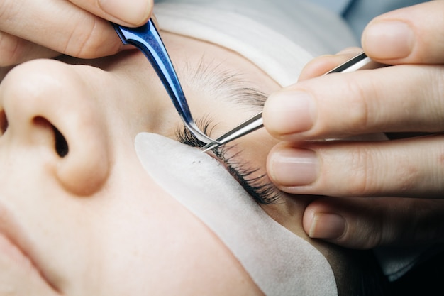 Eyelash extensions. close-up of artificial eyelashes with tweezers. Premium Photo