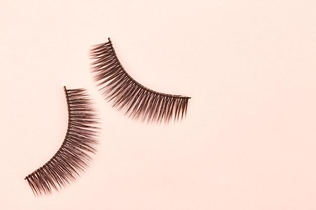 Eyelashes are on pink background Premium Photo