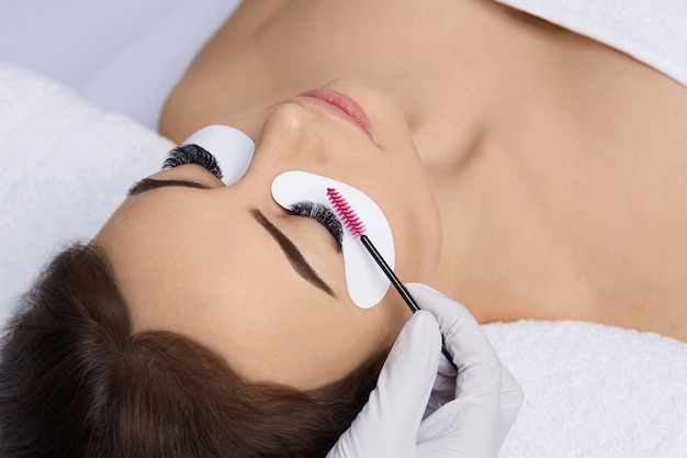 Eyelashes extensions, fake eyelashes, eyelash extension procedure, master and a client in a beauty s