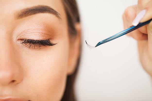 Eyelashes extensions. fake eyelashes. eyelash extension procedure. professional stylist lengthening female lashes. master and a client in a beauty salon Premium Photo