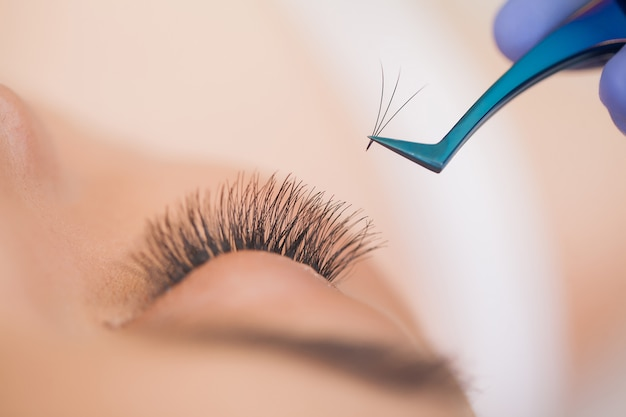 Eyelashes extensions. fake eyelashes. professional stylist lengthening female lashes. Premium Photo