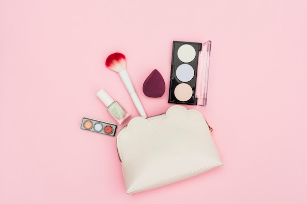 Eyeshadow palette; nail polish bottle; blender; makeup brush and makeup bag on pink background Free Photo