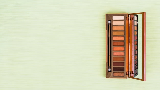 Eyeshadow wooden palette with mirror and makeup brush on mint green backdrop Free Photo
