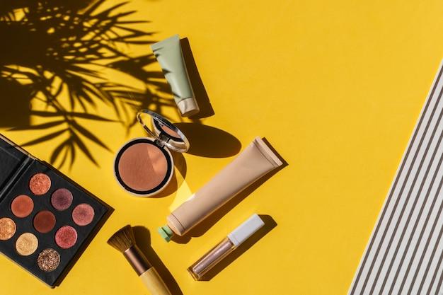 Eyeshadows, powder blush, make up brush on bright yellow Premium Photo