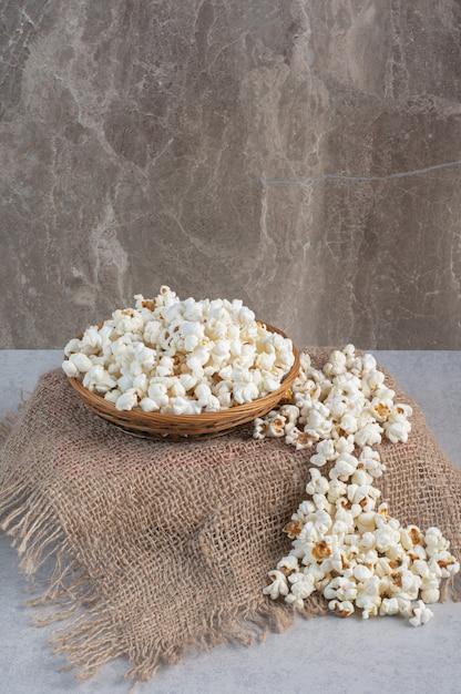 Piedistallo rivestito in tessuto con una ciotola piena di popcorn in cima, accanto a una pila di popcorn su marmo. Foto Gratuite