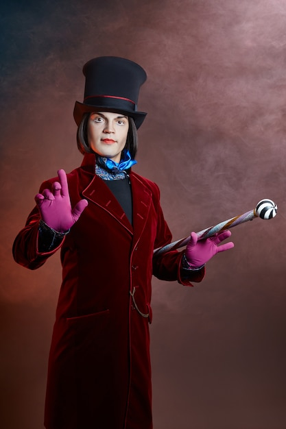 Fabulous circus man in a hat and a red suit posing in the smoke Premium Photo