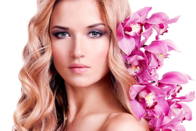 Face of beautiful woman with healthy skin and pink flower over white wall. Free Photo