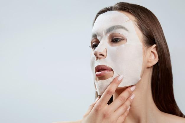 얼굴 관리 및 미용 치료. 천 보습 마스크를 가진 여자입니다. 미용 절차. 스파 및 미용 프리미엄 사진