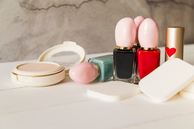 Face cosmetic compact makeup powder with sponges; nail polish bottle and lipstick on table Free Photo