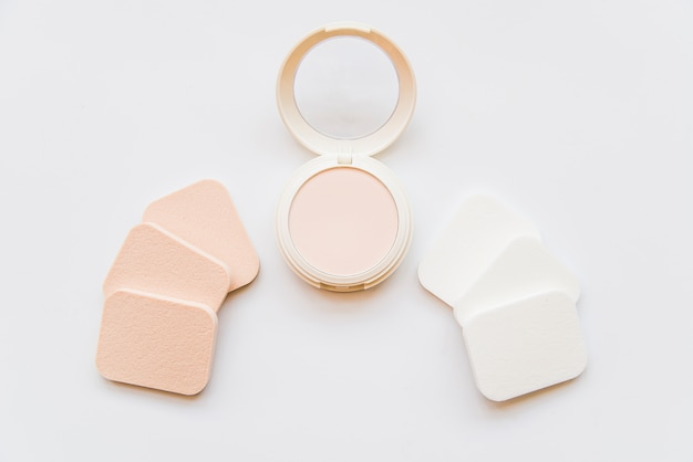 Face cosmetic compact makeup powder with sponges on white background Free Photo