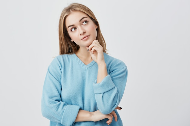 Face expressions and emotions. thoughtful young pretty girl in blue sweater holding hand under her head, having doubtful look while can't decide what clothes to wear on friend's birthday party Free Photo